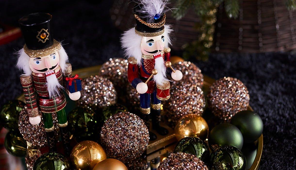 nøtteknakkere og juletrekuler i gull, grønt og rødt
