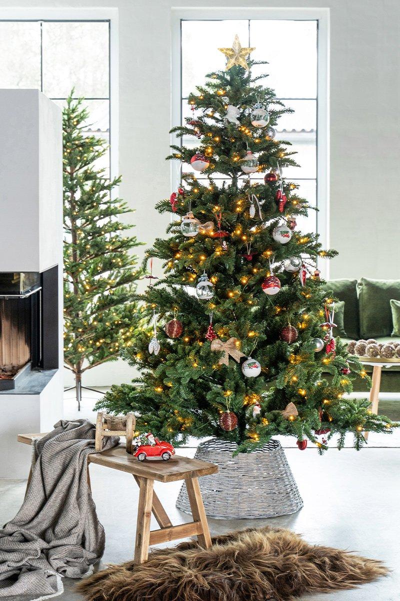stort juletre med pynt og lys i et åpent, lyst rom