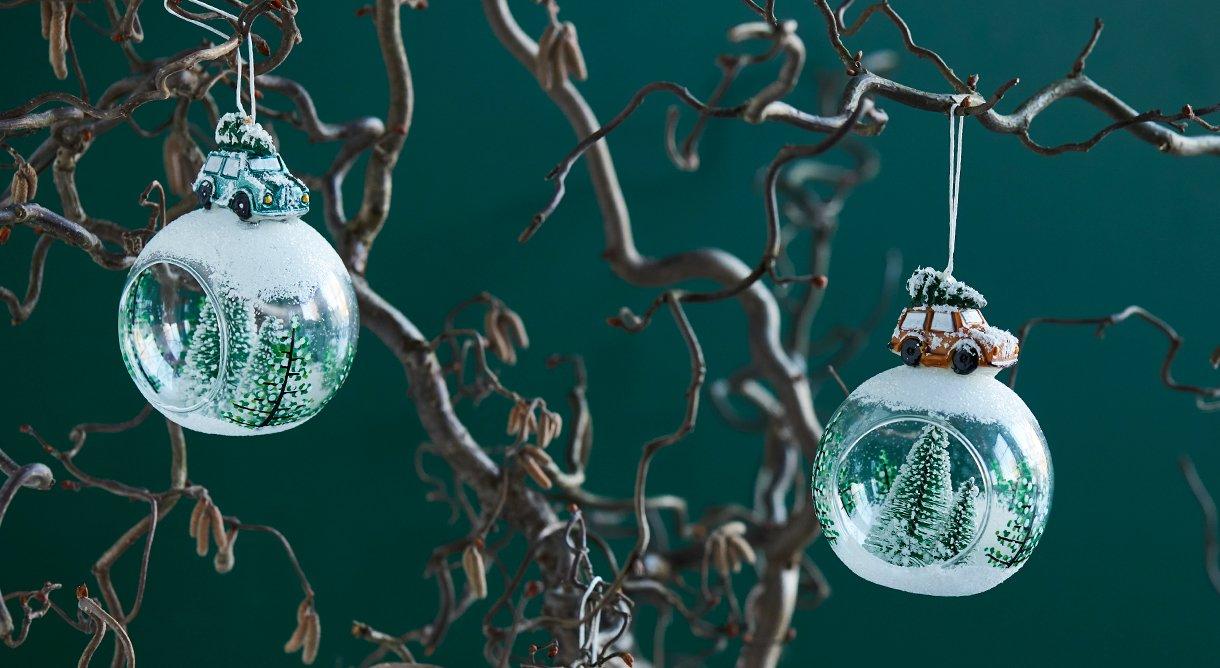 to juletrekuler i grønt glass hengende på kvister