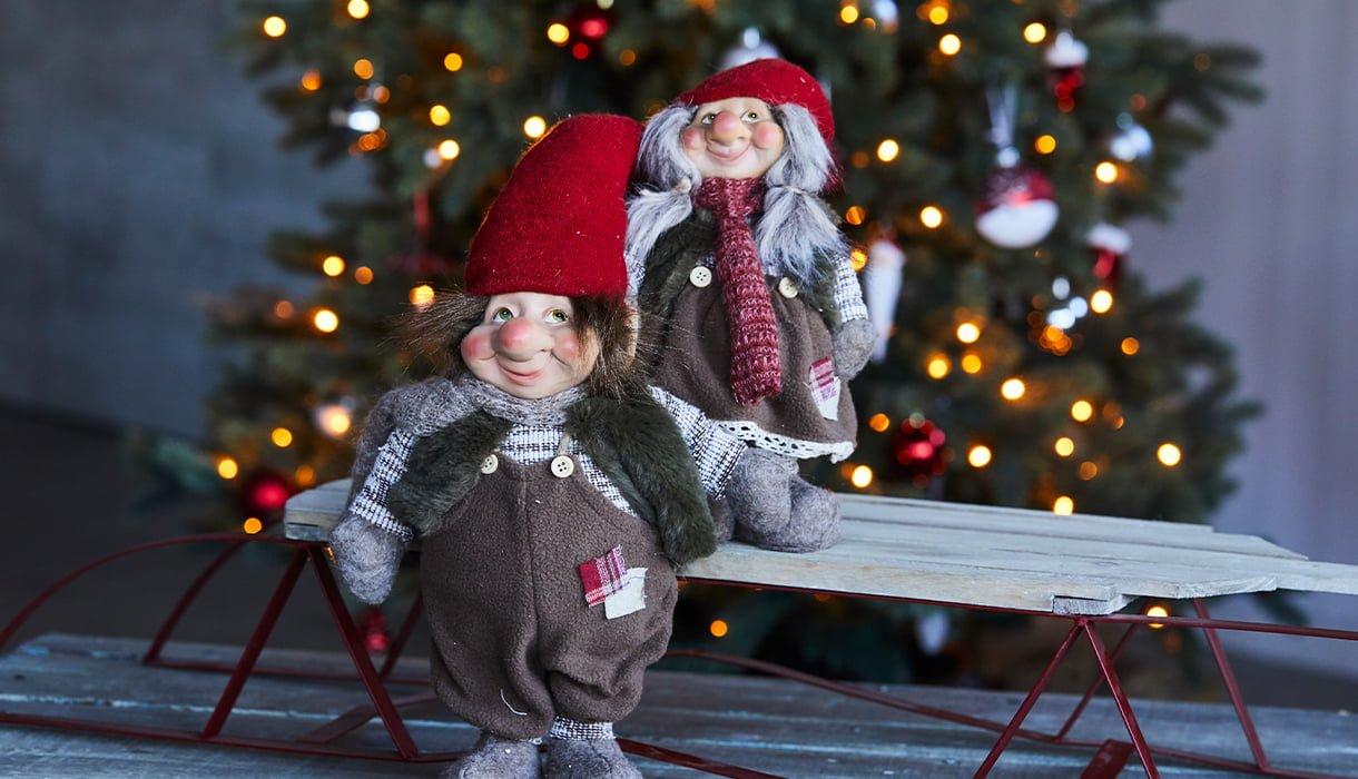 To nisser ned snekkerbukse, på kjelke foran juletre