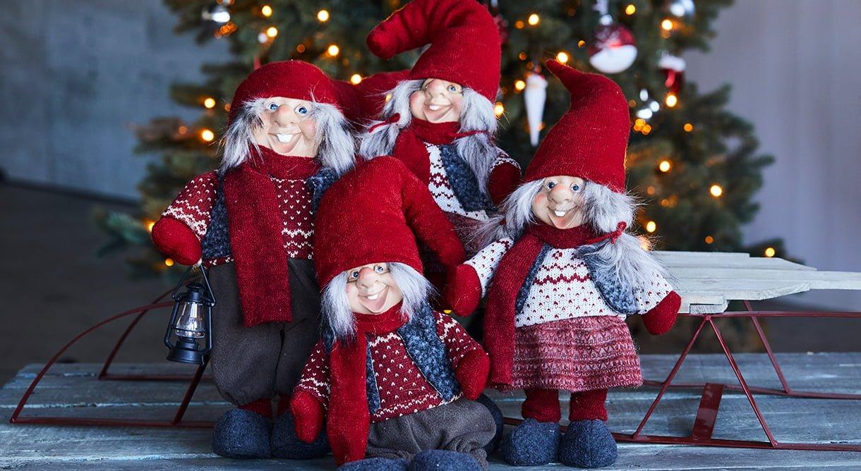 fire glade nisser med røde luer sittende på kjelke foran juletre