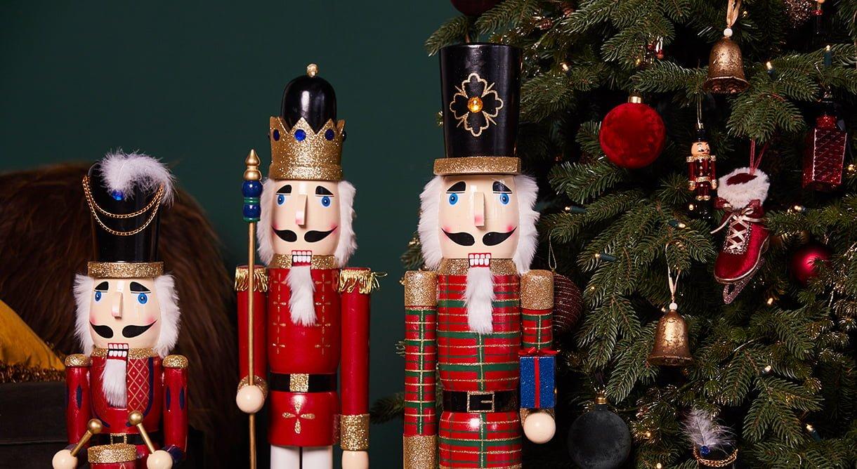 Tre store nøtteknekkere (julefigur) ved siden av et juletre