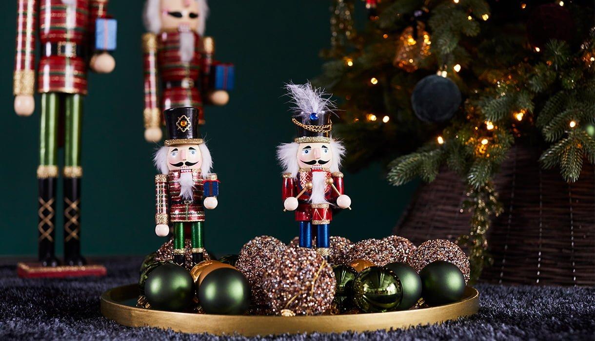 to små nøtteknekkere (julefigurer) i et fat av juletrekuler