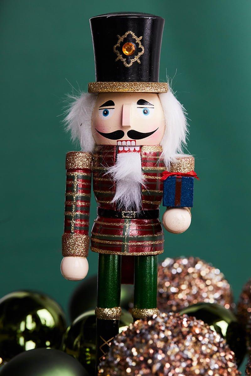 Nærbilde av en liten nøtteknekker sammen med juletrekuler