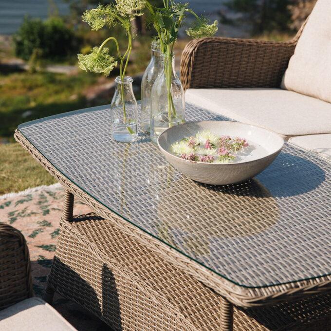 Sofabord Hornbrook med naturfarget kunstrotting dekket med blomster på terrassen