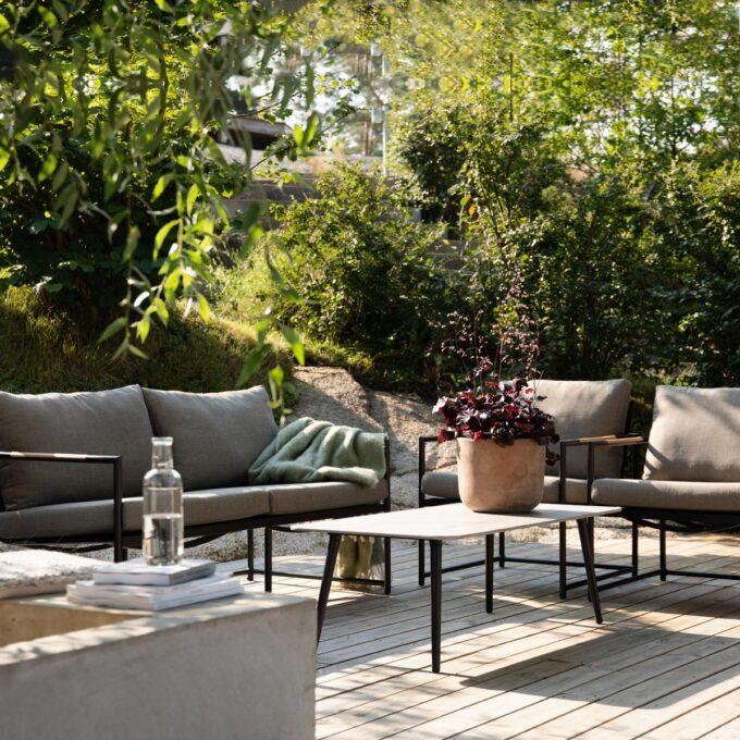 Sofagruppe med 2,5 seter sofa, 2 stoler, bord .sort, med grå puter i olefin og teak detaljer. Bord med grå keramisk topp.