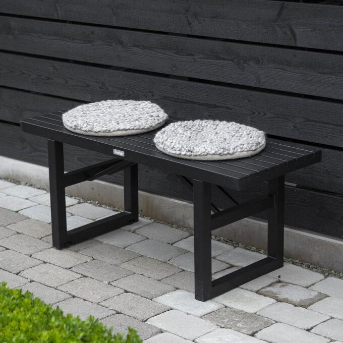 Moderne sort benk i aluminium. Enkelt å flytte rundt og passer fint til sommerfesten.