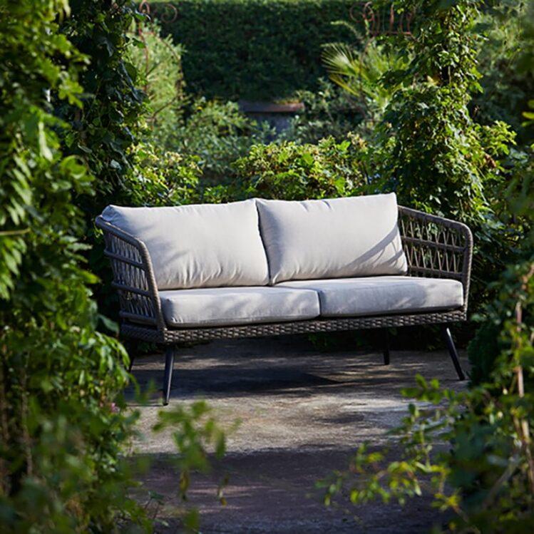 Nydelig 2-seters sofa i naturfarget kunstrotting. Den åpne fletten på kunstrottingen og de lyse putene gir et romantisk