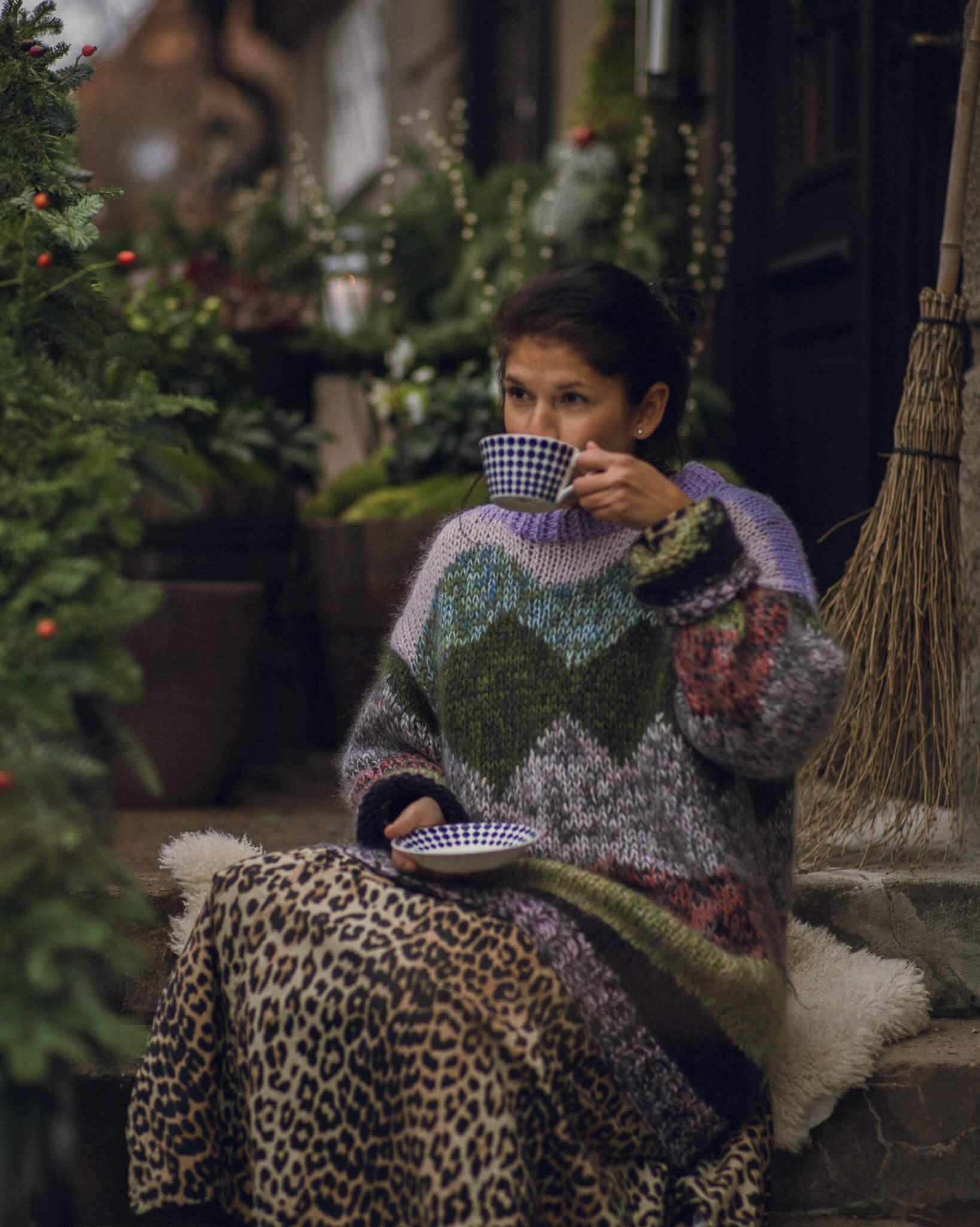 Victoria Dam drikker kaffe i sin grønne hage