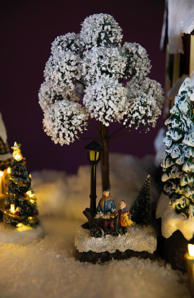 Mennesker under snødekt tre i julebyserien