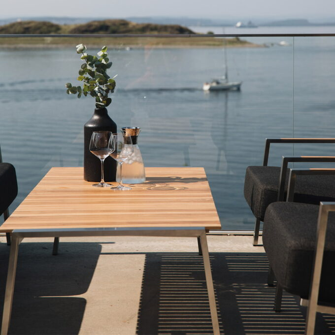 Bord i rustfritt stål og bordplate i teak.