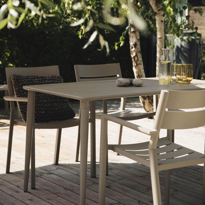 Spisebord i aluminium med pent ribbet bordplater og koniske runde ben.