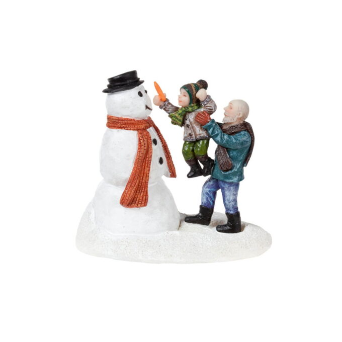 Blir du med og lager snømann? En bestefar med barnebarnet sitt lar snømannen få nese av gulrot.